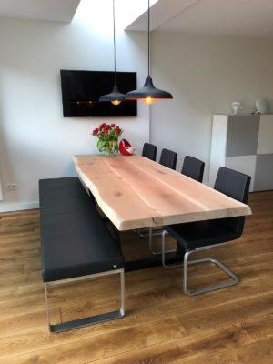 Lange tafel met vier zwarte stoelen en een bank