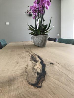 Gevulde knoest in het tafelblad waar een paars bloemstuk op staat